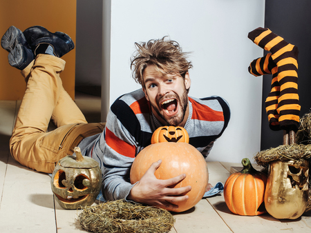 Halloween trick or treat. Pumpkins, striped stockings and wreath. Holidays celebration concept. Man with messy hair happy smiling on floor. Autumn and harvest season. Stock Photo
