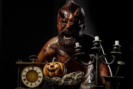 Halloween-satan man met hoorns schreeuwen met pompoen, klok, kandelaar op zwarte achtergrond. Tijd, deadline, licht, vlees, geest concept.