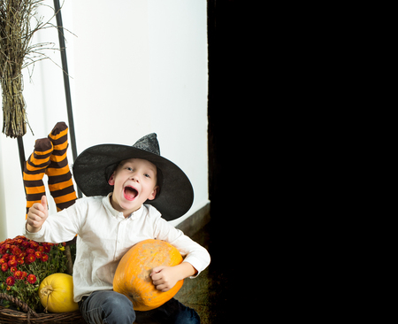 Halloween kid with orange pumpkin in witch hat. Small boy in spider web hat at striped socks. Party and traditional food. Holiday and celebration. Halloween child with happy face, copy space