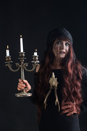 Halloween old woman on black background. Halloween old lady in witch hat with candle. woman in black with long red hair and makeup. holiday celebration. traditional party. Stock Photo