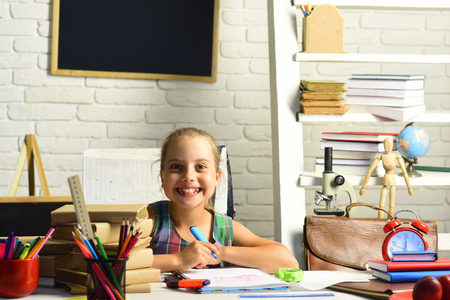 Pupil with books and school supplies. Childhood and back to school concept. Kid with colorful stationery on white wall background. Girl with happy face does homework.