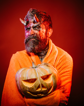 Halloween man devil hold pumpkin on red background. Satan with bloody horns, beard, blood, wounds. Demon in blanket with jack o lantern. Darkness and light concept. Trick or treat. Stock Photo