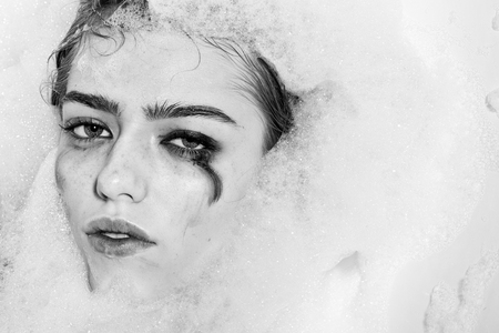 Closeup view portrait of one beautiful sensual sexy attractive young woman with wet bright makeup lying in bath tub with water and lots of white soap foam looking away, horizontal picture