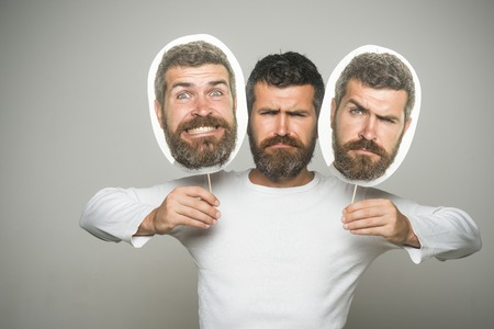 Barber fashion and beauty. Feeling and emotions. Hipster with sad and happy face hold portrait nameplate. Man with long beard and mustache. Guy or bearded man on grey background.