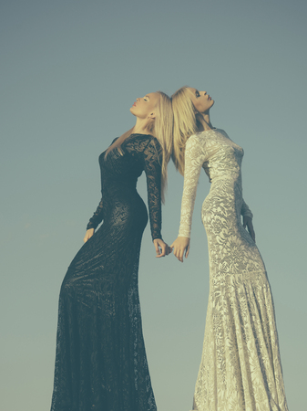 Two girls with long blond hair posing on grey sky. Opposites and contrasts concept. Choice, decision and future. Women wearing black and white dresses. Fashion and beauty.