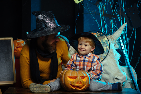 Halloween man and child in witch hat. Boy kid with happy face and bearded man at pumpkin. party and celebration. Halloween Holiday and celebration. Father and small son, fathers day.
