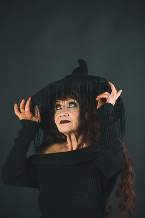 Halloween holiday celebration. Halloween woman in black with long red hair and makeup. old woman on black background. traditional party. old lady in witch hat.
