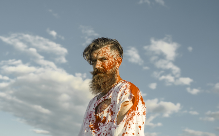Halloween man with red blood splatters on bearded face. Zombie hipster in torn tshirt with bloodstains on grey sky. War soldier or victim concept. Injury, hurt, pain. Evil and horror