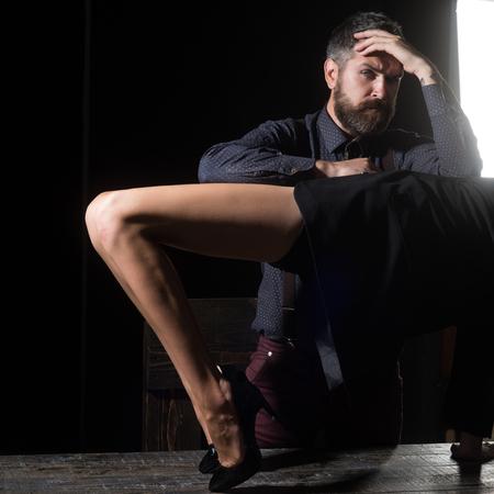 Jongen aan tafel met vrouwelijke benen. Liefde en relaties, domineren. Benen van vrouw in schoenen bij de mens met baard. Romantiek en verliefd. Mens in overhemd op zwarte achtergrond wordt geïsoleerd die.