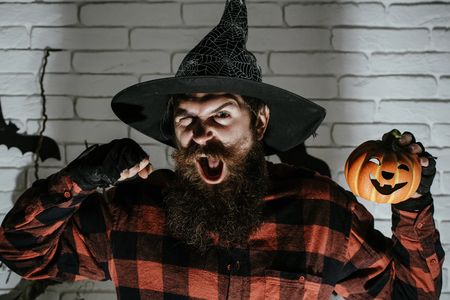 Halloween man with pumpkin and fist in dark shadow. Jack o lantern. Holiday celebration symbols on brick wall. Hipster with beard shouting in witch hat and plaid shirt. Mystery and horror concept.
