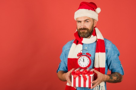 Christmas man hold alarm clock and gift box. New year, xmas holidays celebration. Time to celebrate. Boxing day concept. Hipster in santa hat, scarf on red background, copy space