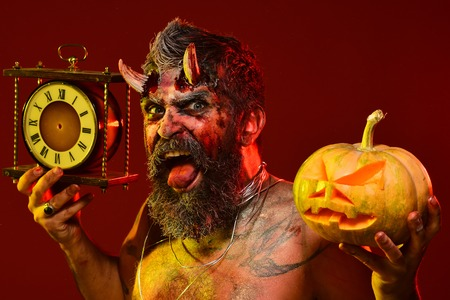 Halloween satan with beard, wounds, blood, tattoo on chest. Devil show tongue with bloody horns on red background. Autumn holidays concept. Time to celebrate. Man demon hold pumpkin and clock.