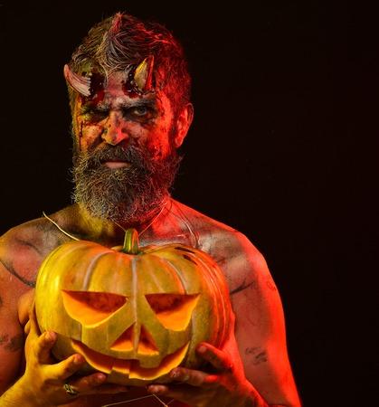Halloween-satan met bloedige hoornen, baard, rood bloed, wonden. De greeppompoen van de mensendemon op zwarte achtergrond. Duisternis en licht concept. Duivel met jack o lantern. Snoep of je leven.