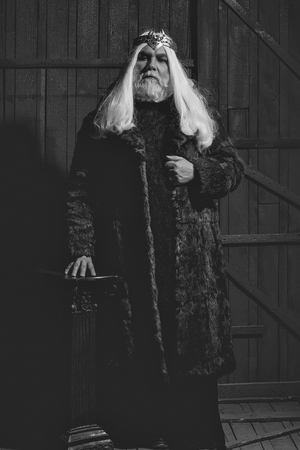 old druid bearded man with long beard on serious face and hair in fur coat and crown with gem stones jewellery on wooden background near column Stock Photo