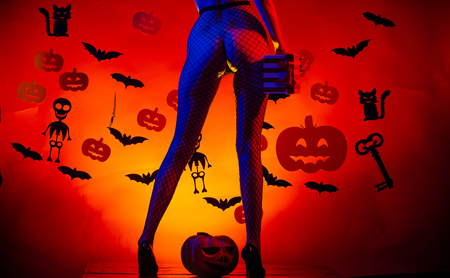 Halloween sexy female legs in fishnet tights and shoes. Legs of girl on skeleton and bat background. party and celebration. Halloween Holiday. buttocks of woman at pumpkin hold gift box.