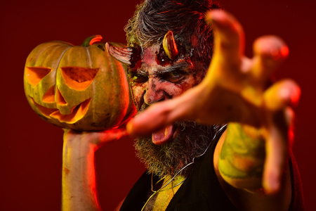 Halloween demon stretch zombie hand with jack o lantern. Satan with bloody horns, beard, blood, wounds. Man devil hold pumpkin on red background. Trick or treat. Darkness and light concept. Stock Photo
