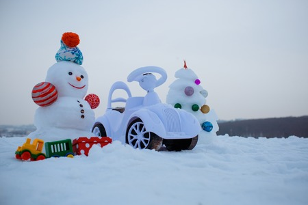 smiley face car: Snowman and toy car on snowy background. Christmas tree and present box on grey sky. Snow sculpture with smiley face on winter day. xmas and new year. Holidays celebration concept.