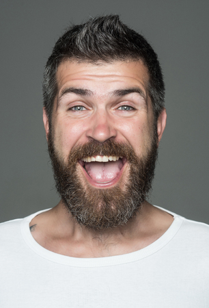 Hipster with happy face. Man with long beard and mustache. Barber fashion and beauty. Feeling and emotions. Guy or bearded man on grey background. 版權商用圖片