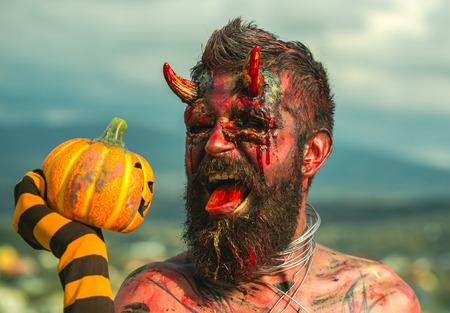 Halloween devil man holding pumpkin in striped sock. Demon with bloody horns on head. Satan with red tongue, beard, blood, wounds on face. Dragon with jack o lantern. Evil, horror, hell concept.