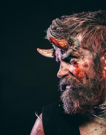 수염, 붉은 피, 얼굴에 상처가있는 할로윈 사탄. 검은 색 바탕에 남자 악마입니다. 지옥, 죽음, 악마, 공포 개념. 머리에 피 묻은 뿔이있는 악마. 휴일 축
