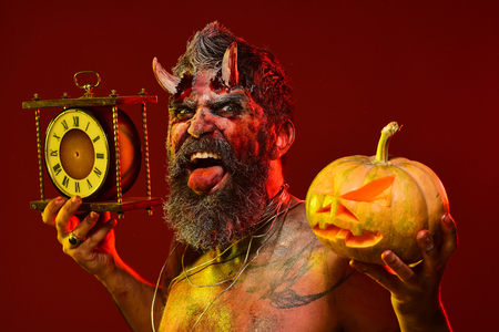 Halloween time to celebrate. Satan show tongue with beard, wounds, blood, tattoo on chest. Man demon hold pumpkin and clock. Autumn holidays concept. Devil with bloody horns on red background.
