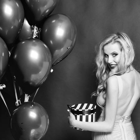 One pretty emotional young happy blonde girl with long curly hair standing with birthday bunch of many red balloons and present box in studio on purple backdrop, square photo
