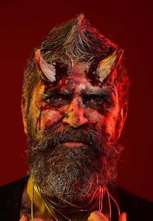 Halloween-mensenduivel op rode achtergrond. Satan met baard, bloed, wonden op het gezicht. Demon met bloedige hoorns op het hoofd. Hell, death, evil, horror concept. Feestviering, cosplay.
