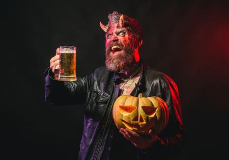 Celebração e festa do feriado de Halloween. O homem com chifres de satanês guarda a abóbora. Diabo sorriso com caneca de vidro. Cerveja da bebida do demônio do moderno no fundo preto. Maus hábitos e conceito de dependência.