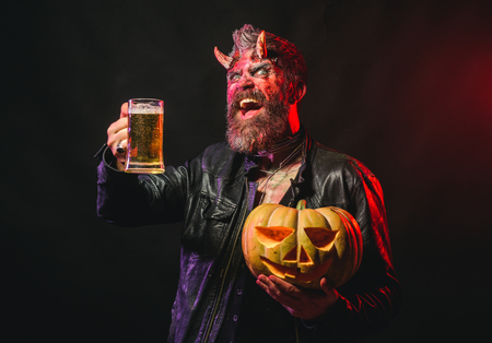 Halloween holiday celebration and party. Man with satan horns hold pumpkin. Devil smile with glass mug. Hipster demon drink beer on black background. Bad habits and addiction concept.