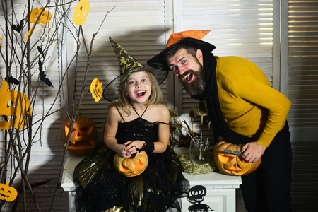 Father and daughter with Halloween decor. Wizard and little witch in hats hold jack o lantern. Girl and bearded man with cheerful faces on red spooky carnival room background. Halloween party concept