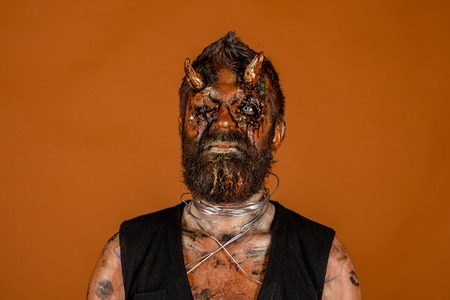 Halloween man devil on orange background. Demon with red blood eyes, beard, wounds on face. Satan with bloody horns on head. Evil, horror, hell, death concept. Holiday celebration, cosplay.