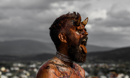Halloween hell, evil, horror, darkness concept. Demon man with beard showing tongue. Vampire or dragon with open mouth. Satan with red blood and wounds on face. Devil head with bloody horns. Stock Photo