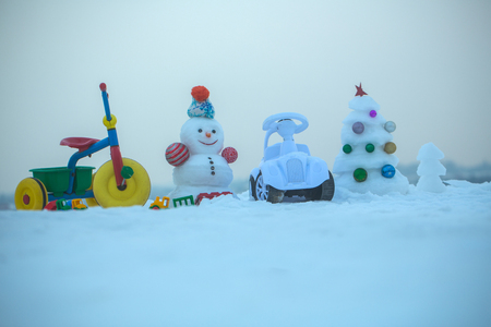 Christmas and new year. Tricycle and toy car on snowy background. Snowman and snow xmas tree on blue sky. Winter holidays celebration concept. Festive surprise and presents. Stock Photo