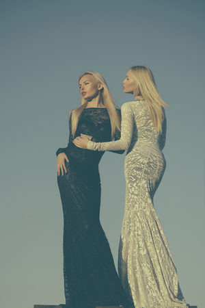 Opposites and contrasts concept. Women wearing black and white dresses. Fashion and beauty. Choice, decision and future. Two girls with long blond hair posing on grey sky. Stok Fotoğraf