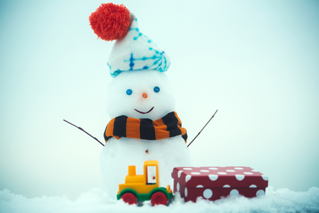 Snow sculpture with smiley face. Christmas and new year. Toy train and red present box. Winter holidays celebration concept. Snowman in hat and scarf on blue background. Stock Photo
