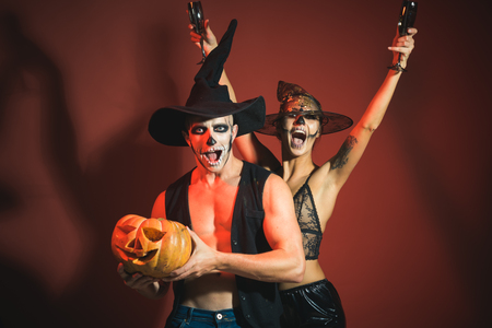 Halloween Zombie party and horror. Holiday and celebration. woman and man has happy face in witch hat. Halloween couple with makeup background. Couple in love with pumpkin and wine glass. Stock Photo