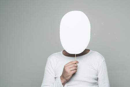 コピー スペースは、灰色の背景に紙銘板隠れて顔をもつ男 写真素材