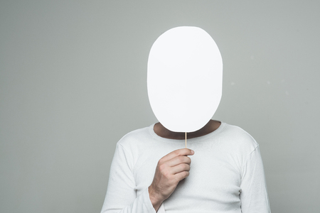 man with paper nameplate hiding face on grey background, copy space 版權商用圖片