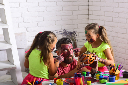 Halloween Holiday and party celebration. Halloween children with happy face in paint. family with colorful paint. Kids or small girls with bearded man father hold pumpkin. Art and color painting.