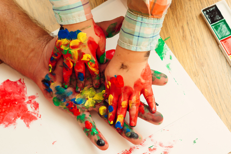 Handprint painting concept. Hands and fingers drawing with multicolor paints on white paper. Arts and crafts. Fathers day, family love and care. Imagination, creativity and freedom.