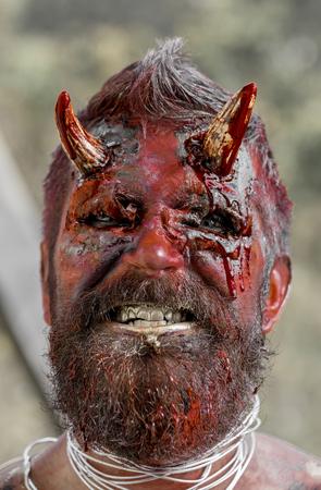 Halloween-demonmens met baard die tanden toont. Satan met rood bloed en wonden op de gelaatshuid. Duivelskop met bloedige hoorns. Draak, schepsel, witcher. Verleiding, hel, kwaad, verschrikking, duisternisconcept.