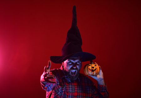Halloween man with scary face and jack o lantern. Mystery and magic concept. Autumn holiday celebration. Trick or treat. Hipster in wizard hat holding pumpkin on red background.