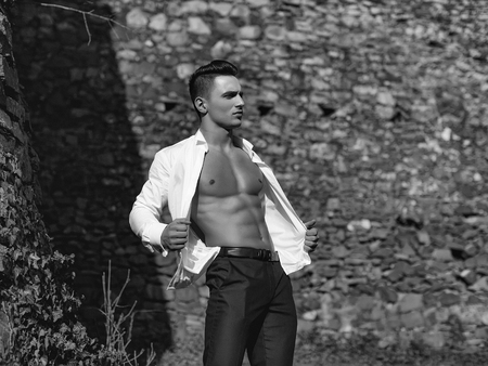 Man half face bare-chested young handsome sensual model in white shirt gaped open and black trousers poses outside grey color filtre on masonry background
