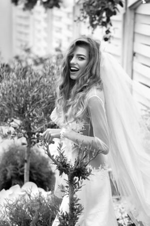 young sexy woman with long blonde hair and pretty smiling face in wedding white dress and bride blue veil on green garden background