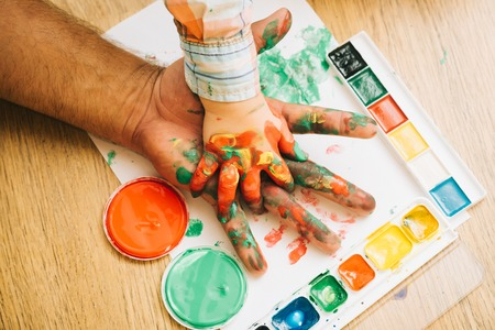 Support and protection. Fathers day and family. Care, love or adoption concept. Hands in colorful paints and multicolor palette on white paper. Arts and handprint painting.