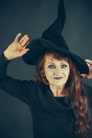 halloween old woman with long red hair and nakeup in witch hat and antler on black background
