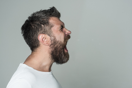 man with long beard on angry face on grey background, copy space
