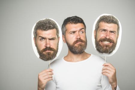 灰色の背景に紙の銘板と悲しい顔に長いひげを持つ男