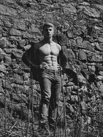 男裸-な胸の若いポーズは、壁画の背景上のジーンズ屋外でセクシーなモデル
