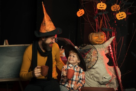Halloween Father and small son drink from tea or milk cup. Holiday and celebration. Boy kid with happy face and bearded man at pumpkin. party and celebration. Halloween man and child in witch hat.